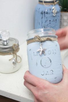 Add some organization and a touch of coastal style to the bathroom with these painted mason jars. bottle crafts for bathroom Beachy DIY Mason Jar Containers Mason Jar Projects, Mason Jar Crafts, Crafts With Mason Jars, Pickle Jar Crafts, Beach Mason Jars, Uses For Mason Jars, Mason Jar Christmas Crafts, Mason Jar Lanterns, Mason Jar Sconce