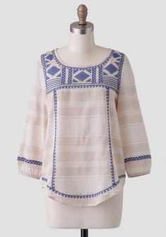 Rendered in a light beige cotton with a white striped print, this charming blouse features royal blue, geometric cross-stitch embroidery.