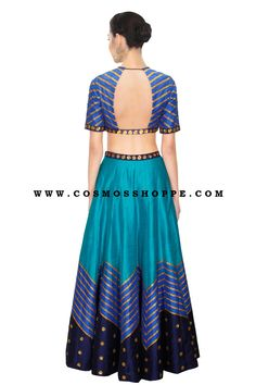 Featuring a teal blue raw silk lehenga with printed lines and navy blue border embroidered with gold sequins flowers.  It is paired with teal blue raw silk blouse with zig-zag printed lines and gold sequins flowers.  Title : Teal blue embroidered lehenga set  Color : Blue Fabric : Raw Silk Type : Embroidered, Printed Occasion : Festive, Wedding, Ceremony. Neck Type : Rount Neck Sleeve Type : Half Sleeves