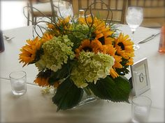curly willow entwined through bright yellow sunflowers and green hydrangea make an inviting centerpiece. www.TheLoftFlorist.com
