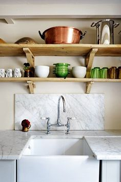Old elm pieces were used to craft the shelves in the kitchen above Carrara-marble-topped units made by Charles Hurst. Planks of reclaimed pine from an industrial building span the floor.