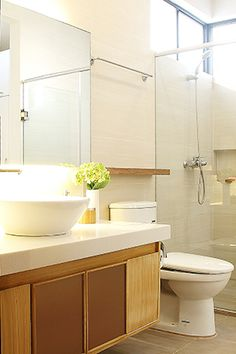 The only element changed in the bathroom is the conventional pedestal type lavatory. Gwen replaced it with a surface mounted sink over a custom-made lavatory cabinet topped with a speckled solid surface. To complete the sophisticated look of the space, the designer also added a mirror with cove lighting underneath, a solid wood ledge above the water closet, and a shower enclosure.