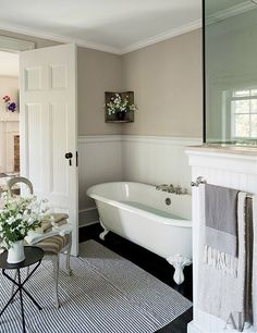 An antique chair rests on a striped rug in the master bath | archdigest.com