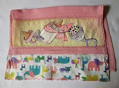 Detalhe do motivo pintado a mão na fralda de boca rosa, com motivos pintados para bebê 'mamadeira, chupeta e chocalho''.