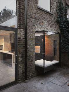 neat oriel graphite brick + black carpentry + warm light inside