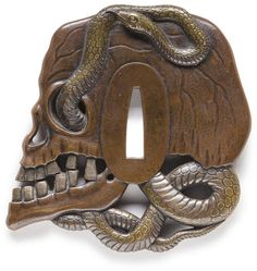 A copper and sentoku tsuba Edo period (19th century), after Iwamoto Konkan / Designed as a snake entwined around a skull, the serpent carved in the round and the teeth highlighted in silver overlay, inscribed Konkan