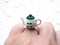 This is cute! There is a teapot with cherries on it!  It is on a silver tone adjustable band that will fit most ring sizes. It measures about 2.7 cm wide.  SouZouCreations' products are made with attention to detail, creativity and long lasting dependability.