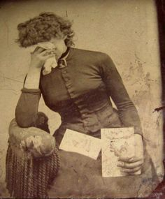 Woman documenting her mourning holding a letter or photo. Circa 1870 tintype.