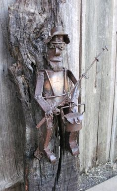 Tall Fisherman Metal Sculpture On Black Oak Board is an original welded metal sculpture by Billy V. Ackerman. Bill used recycled and repurposed pieces of metal in the process of welding the fisherman. The creel even opens up. The sculpture is mounted on a Black Oak board. The