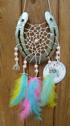 Glücksfänger Sun mit weißem Baumwollgarn, rosa und weißen Perluttperlen sowie Ornamentmetallperlen und kristallförmigen Perlen. Die Federanhänger sind mit regebogenfarbenen Flauschfedern gestaltet. Der Anhänger weist ihn als Original-Glücksfänger aus.
