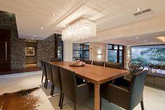 This outstanding dining area features a simple wood table with deep chocolate, snake skin textured high back chairs. An impressive crystal chandelier looms above, while additional lighting flows from modern sconces, recessed lighting, and a large picture window. An animal hide area rug graces the ivory tiled floors, while the impressive stonework of the walls adds additional texture and beauty.