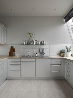 Grå flater og elementer i stål på kjøkkenet fra Bulthaup. På benken: Keramikkpotte Solid.