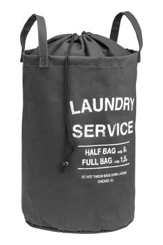 Laundry bag: Laundry bag in ecru cotton twill with a text print, two handles, a plastic coating on the inside and a top section in thinner fabric with…
