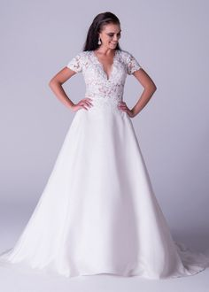 Viola Chan wedding dress, Structured A-line dress with mikado skirt and low plunging neckline in bold lace applique. This on trend gown is sure to make heads turn.