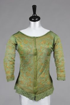 A rare green and yellow knitted silk woman's jacket, probably Italian, mid 17th century, the front and back panels with gold thread and yellow silk scrolling foliage and blossom, with textured chequered borders