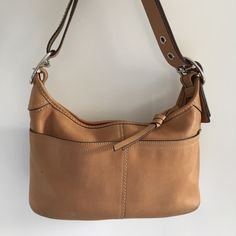Coach Leather Handbag in Tan Brown Preowned Coach Leather Handbag in Tan Brown. Has signs of regular wear all around. Great storage space and compartments inside. Very nice embossed Coach Logo on the bottom of the bag. Please look at pictures for better reference. Happy shopping!! Coach Bags Shoulder Bags