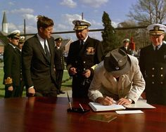 President Kennedy watches as Vice President signs his autograph.
