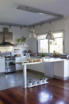 """A tono, la cocina usa muebles y estantes en madera laqueada, y una mesada que desemboca en una barra en """"L"""" (Johnson Amoblamientos) iluminada por dos lámparas de aluminio."""