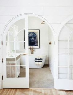 All White Bathroom With Arched Doors.