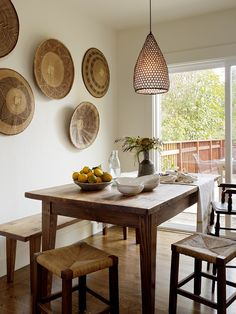 rustic dining room with basket on the wall, wooden dining table and wooden stools, woven pendant light