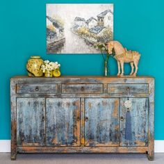 Distressed Chinese blue grey sideboard. c.1930 with rustic wooden background, originating from the Dongbei Province. Handmade exquisitely with removable shelves and doors, this vintage Asian solid wood cabinet three drawers above and four cupboards below, all with decorative brass hardware. #chineseantiques #chinesefurniture #orientalfurniture #storage