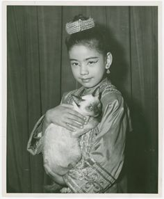 [Carole Luna (Royal Child replacement) holding Somawadi the cat backstage at The King and I]  [King and I (musical), by Rodgers & Hammerstein] (195?)