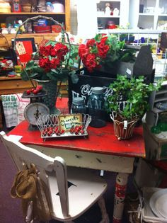 scale, geraniums, wire basket, wooden tool box, red table