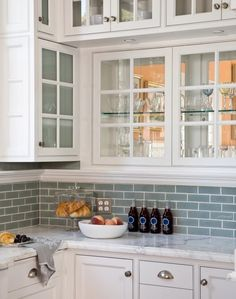 Blue subway tile backsplash with white cabinets.