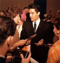 Elvis signs autographs after completing the press conference held in Memphis, Tennessee, on February 25, 1961 (to honor Elvis for his numerous contributions to local charities).