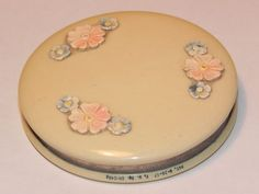"""rare powder compact with a patent reference to 1917 - in lovely condition, it is made of bakelite, or ivorine celluloid, has 3 pretty carved flowers to the top and an unusual sifting mechanism - simple fitted top with a mirror insert - measuring c 2.1/4"""" inch (5.6cm)"""