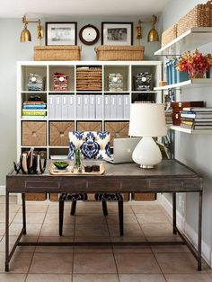 A neatly organized bookcase is filled with magazine holders, textured baskets, stacks of books and larger lidded baskets on the top of the bookcase (don't forget about the top - it's a great opportunity for more storage and / or accessories). The desktop is kept clean with a tray white lamp.