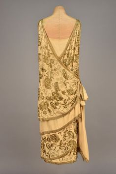 BEADED EVENING DRESS, c. 1920. Sleeveless ivory silk having wrap front with side tie, angled draping and side streamers lavishly decorated in gold beaded floral, silk under-dress. / Back View.