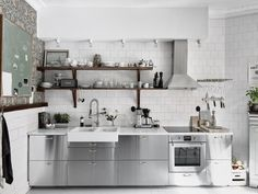 This Scandinavian kitchen from Entrance features IKEA cabinets with stainless steel cover panels. Savings Stretchers: 8 Times Inexpensive Materials Looked Really Great in the Kitchen Swedish Kitchen, Scandinavian Kitchen, Scandinavian Apartment, Scandinavian Interior, Beautiful Kitchen Designs, Beautiful Kitchens, Apartment Kitchen, Kitchen Interior, Ikea Cabinets