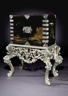 A Japanese Lacquer Cabinet on Silvered stand with gilt chinoiseries