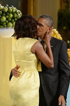 U.S. President Barack Obama kisses First Lady Michelle Obama during the second annual 'Kids' State Dinner', in the East Room of the White House July 9, 2013 in Washington DC. The 'State Dinner' features a selection of winning recipes and recognizes fifty-four winners representing all US states, three territories and the District of Columbia. (July 8, 2013 - Source: Pool/Getty Images North America)