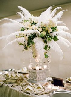 "For a ""Gatsby-style"" wedding - lavish, tall centerpieces filled with elegant roses and luxe feathers ~ http://www.stylemepretty.com/collection/2199/picture/1466219/"