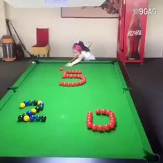 A child performs a pool table trick shot. https://i.imgur.com/4H8HWF3.gif
