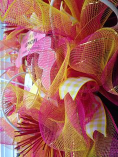 when life gives you lemons make lemonade!! Multi color pink and yellow deco mesh wreath with white roping, pink tubing, and yellow checkered ribbon, and lemonade sign!