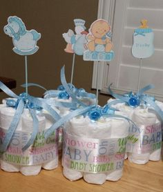 """Mini Diaper Cake Center pieces.   7 newborn diapers, 8 rubber bands, 2 sizes of ribbon, pacifiers, 8"""" favor picks. 1. Roll each diaper & hold together w/ a rubber band. 1 diaper in the middle & 6 diapers around it. Hold them all together w/ another rubber band. 2. Hot glue a 3"""" wide piece of """"Baby Shower"""" ribbon around the diaper roll. 3. Tie """"It's a boy"""" 1/4"""" ribbon to 2"""" pacifiers. 4. Take a favor pick & put 3 pacifiers on the stick then carefully put the stick in the middle of the diaper…"""