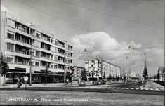 Slotermeerlaan in noordelijke richting, vanaf de kruising met de Burgemeester Roëllstraat. Drie flatgebouwen met winkels, o.a. een VANA supermarkt. De eerste zijstraat links, is de Lodewijk van Deysselstraat. 1957-1960