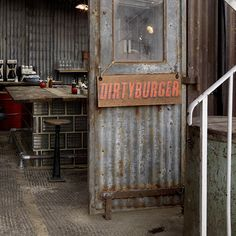 It looks like a corrugated iron shed because it is, at least on the surface, although the central dining island and the fly-trap looking light fittings are examples of sophistication not apparent at first glance...