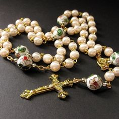 A pink pearl rosary handmade with cloisonne beads in a pretty white floral pattern and lots of golden accents.  This handmade rosary is designed with 8mm pink pearls as the Aves and the cloisonne bead