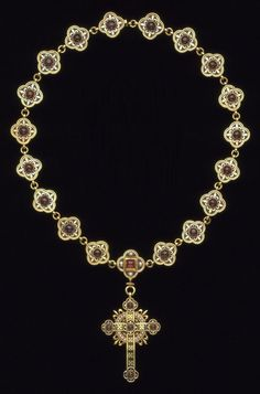 Victorian Gothic Revival necklace and cross, designed by Pugin and made by John Hardman & Co., circa 1843. Enamelled gold, set with cabochon garnets and pearls. Made for Louisa Burton, the second wife of the architect A. W. N. Pugin. Pugin's account with John Hardman & Co. of Birmingham contains an entry on 21 December 1843 for 'A Gold enamel Chain & Cross' costing £47. 15s. © Victoria and Albert Museum, London