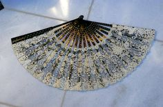 $995 1880. Hand-made lace of floral decoration upon black tulle spread across the tortoise shell sticks and guards. The shell sticks and guards boasts exquisite pique work: inlaid silver polka dots. This theme is carried out on the lace with hand sewn shimmering sequins. In all a dazzling sparkling fan! It comes with the original box, satin lined and bearing the name of the maker: Ernest Kees, 9 Boulevard des Capucines-Paris. The tooled leather box is also in good condition, some modest wear