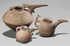 THREE IRANIAN POTTERY SPOUTED VESSELS CIRCA EARLY TO MID 1ST MILLENNIUM B.C. Including a small globular jug; one with a goat-form handle; and one carinated, with a concentric semi-circles incised on the top section; together with two Iranian bronze vessels, circa 1st Millennium B.C.; and an Islamic bronze mortar Largest: 16¼ in. (41.2 cm.) long (6)