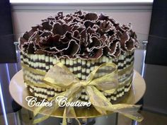 Choclate Ruffles. Purchased Zebra Striped Chocolate Cigarellos around sides of iced cake. Chocolate ruffles on top made with la Girolle chocolate ruffler.