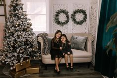 holiday christmas family photo mini session tree gold gifts wreaths little girls sisters black dresses sofa couch