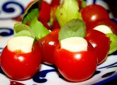 **Caprese Tomato Shooters** Easy and Cute!!  Scoop out and discard pulp and stem of the cherry tomatoes. Invert tomatoes onto paper towels to drain. Sprinkle with sea salt. Slice each mozzarella stick into eight rounds. Turn tomato halves over and drizzle with oil. Wrap a leaf of basil around a slice of cheese, like a taco, then insert into a tomato.