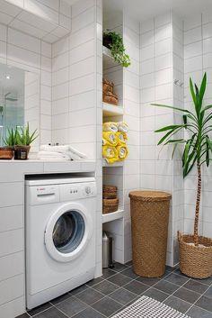 Murowany blat nad pralką i półki wyłożone takimi samymi kaflami jak ściany tworzą lekką wizualnie zabudowę tej łazienki. A przy tym neutralne tło dla kolorowych ręczników i wiklinowych koszy. Te ostatnie, podobnie jak rośliny doniczkowe dodają wnętrzu salonowej przytulności.