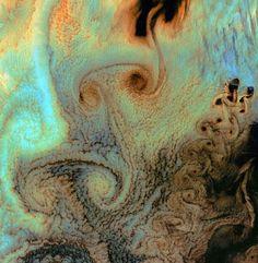 """Tourbillons sur les îles de l'Alaska. Sur cette image, le vortex (tourbillon) spectaculaire s'est créé lorsque les vents principaux du Pacifique nord sont rentrés en contact avec les îles d'Alaska. Ce phénomène météorologique porte le nom d'""""allées de tourbillons de Karman"""". Cette photo étonnante a été prise par le satellite américain Landsat 7. © Nasa"""